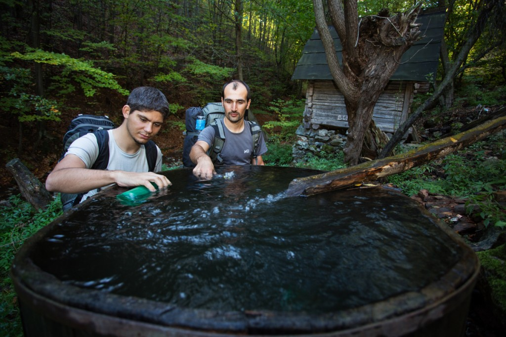 Hikers (Adrian Grancea, left & Dan Dinu) replenishing their water supplies at an old mill in the forest outsde the village of Isverna. Geoparcul Platoul Mehedin?i, Romania.