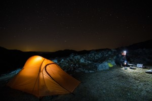 Hiker (Dan Dinu) heating up water beside his tent under a starry sky over a rocky limestone ridge in Mehedinți Plateau Geopark, Romania