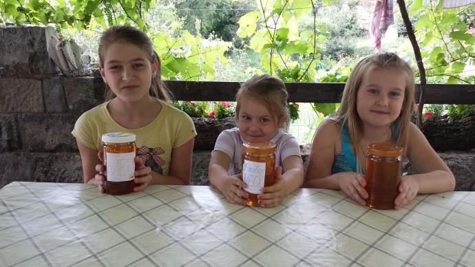 Petra, Paula, and Antonija at the Knežević family home displaying jars of honey harvested from their beehives.