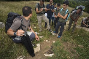 Umberto Esposito, mountain guide and CEO at Wildlife Adventures, partner of Rewilding Europe in the Apennines, showing wolf scat while leading a group for a bear watching excursion. Abruzzo National Park.