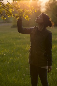 Woman looking at oak leaves. Piani Palentini, Scurcola Marsicana, Abruzzo, Italy. May 2014