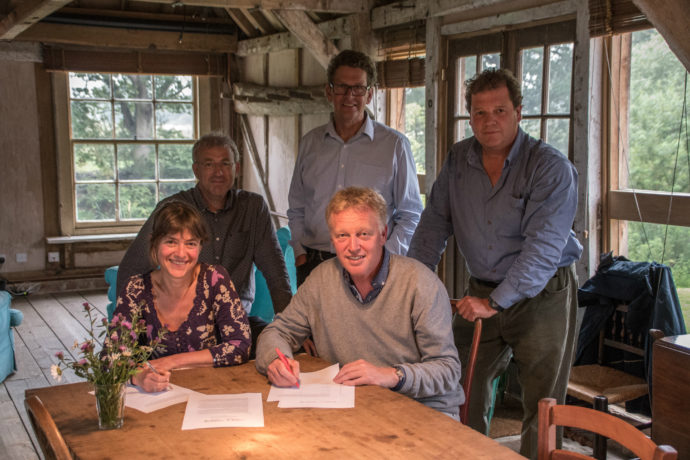 Rebecca Wrigley (Director Rewilding Britain) and Frans Schepers (Managing Director Rewilding Europe) signing the Collaborative Rewilding Agreement on 27 June at the Knepp Castle Estate. In the background (left to right): Wouter Helmer (Head of Rewilding in Rewilding Europe), Paul Jepson (Board member of Rewilding Europe) and Charlie Burrell (Chairman of the board of Rewilding Britain).