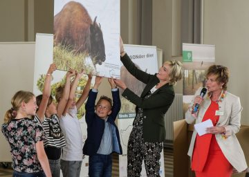 Princess Laurentien presenting the bison board with school children at the official opening of the European bison grazing project in Radio Kootwijk, Veluwe area, 13 June 2016.
