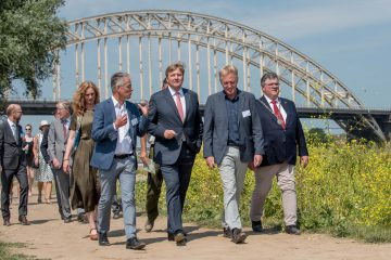 King Willem-Alexander (middle) is guided by Frans Schepers (right) and Professor Hans de Kroon (left) during a short walk on the floodplains of the River Waal.