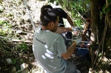 Members of the Rewilding Apennines team install an electric fence in a bear corridor.