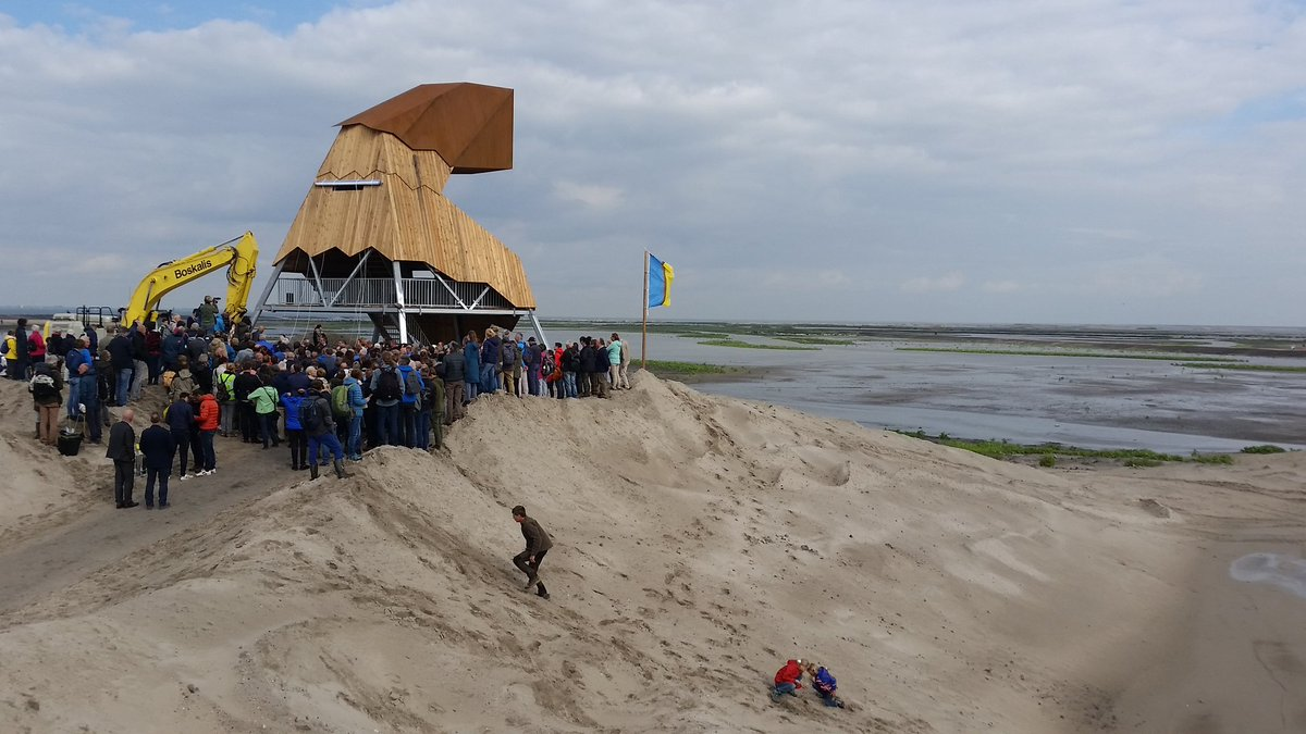 Crowds of people gather at the opening of an island created in the centre of the Markermeer as part of the Marker Wadden rewilding project.