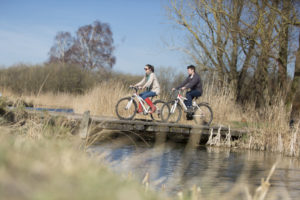 Visitors cycling at Wicken Fen National Nature Reserve, Cambridgeshire.