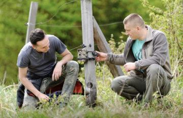 Bison rangers checking wildlife camera