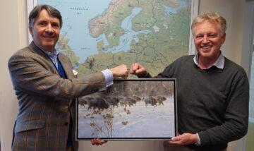 Frans handing over a painting of a European bison herd to Wiet de Bruijn after leaving the Supervisory Board