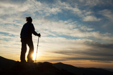 Walker silhouetted at sunset on Braeriach, Cairngorms National Park, Scotland